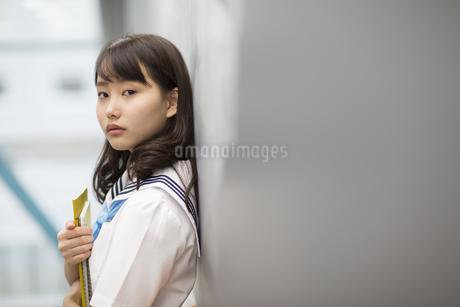 黒板に教材を持って寄り掛かって立つ女子学生の写真素材 [FYI02968515]
