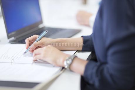 打ち合わせ中にメモを取るビジネス女性の手元の写真素材 [FYI02968516]