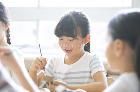 絵具の筆で色を塗る女の子の写真素材 [FYI02968521]