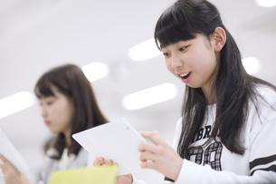 タブレットPCを持って授業を受ける女子生徒の写真素材 [FYI02968523]