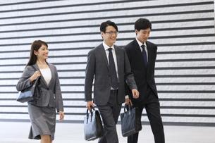 オフィスビルのロビーを歩くビジネス男女の写真素材 [FYI02968527]