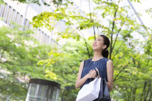 街角で上を見上げ微笑む女性の写真素材 [FYI02968534]