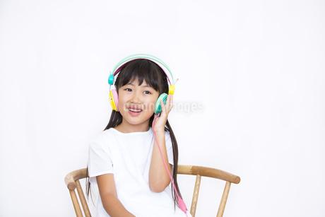 ヘッドフォンを付けて微笑む女の子の写真素材 [FYI02968536]