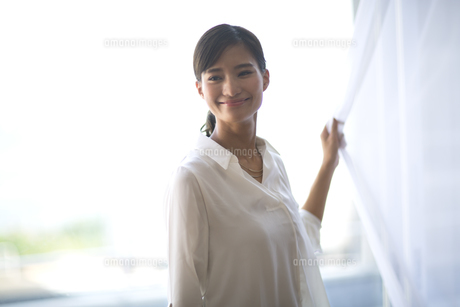 カーテンの傍で微笑む女性の写真素材 [FYI02968541]
