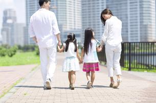 手をつないで遊歩道を歩く家族の後ろ姿の写真素材 [FYI02968552]