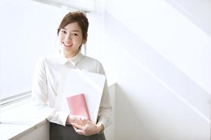 資料と手帳を持って微笑むビジネス女性の写真素材 [FYI02968554]