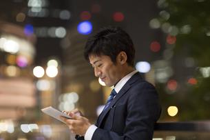 夜の街を背景にタブレットPCを見て微笑むビジネス男性の写真素材 [FYI02968555]