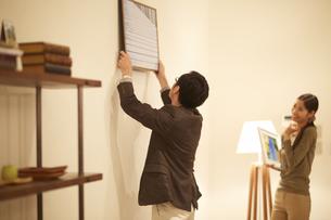 壁に写真を飾る男性とそれを見る女性の写真素材 [FYI02968556]