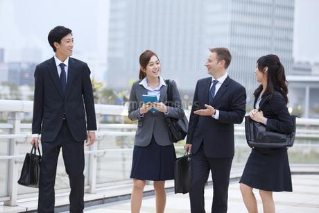 オフィスビルを背景に笑いながら歩くビジネス男女の写真素材 [FYI02968557]