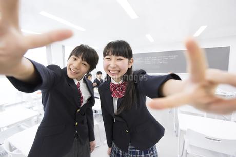 教室でポーズをとって笑う男子学生と女子学生の写真素材 [FYI02968564]