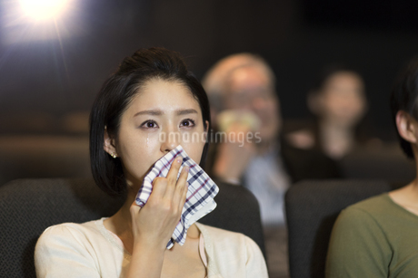 映画館で涙をこぼす女性の写真素材 [FYI02968566]