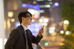 夜の街を背景にスマートフォンを持ち遠くを眺めるビジネス男性の写真素材 [FYI02968568]
