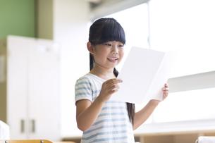 授業中に作文を読む小学生の女の子の写真素材 [FYI02968569]