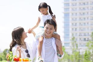 肩車して遊歩道を歩く家族の写真素材 [FYI02968570]