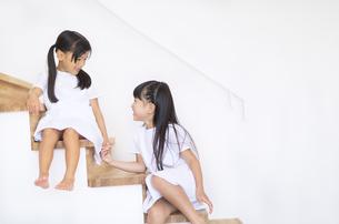 階段に座って手を繋ぐ女の子の写真素材 [FYI02968571]