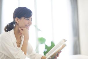手に本を持ち微笑む女性の写真素材 [FYI02968577]