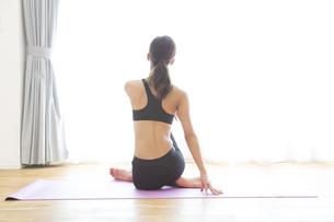 ヨガマットの上でストレッチをする女性の後ろ姿の写真素材 [FYI02968578]
