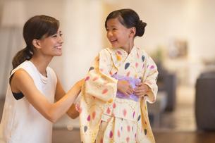 子供に浴衣を着せる母親の写真素材 [FYI02968580]