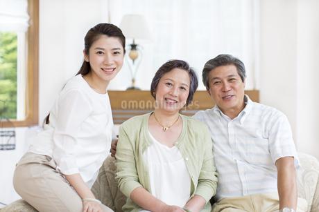 笑顔で寄り添うシニア夫婦と娘の写真素材 [FYI02968581]