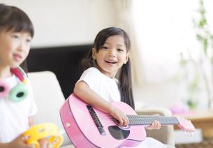 ソファーに座ってギターを弾く女の子の写真素材 [FYI02968583]