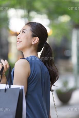 街角で上を見上げ微笑む女性の写真素材 [FYI02968591]