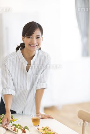 ダイニングテーブルで料理の準備をする女性の写真素材 [FYI02968596]