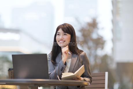 街中で顎にペンを当て上を見上げ微笑むビジネス女性の写真素材 [FYI02968601]