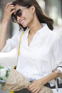 花束を持ったサングラスをかけた女性の写真素材 [FYI02968602]