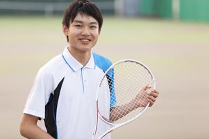テニスラケットを持って笑う男子学生の写真素材 [FYI02968607]