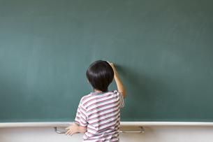 黒板に文字を書こうとする男の子の写真素材 [FYI02968609]
