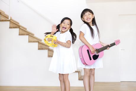 タンバリンを叩く女の子とギターを弾く女の子の写真素材 [FYI02968612]