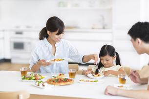 ダイニングテーブルで食事を楽しむ家族の写真素材 [FYI02968620]