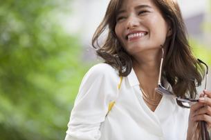 手にサングラスを持って笑う女性の写真素材 [FYI02968621]