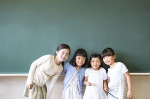 黒板の前に並んで立って笑う女の子4人の写真素材 [FYI02968624]