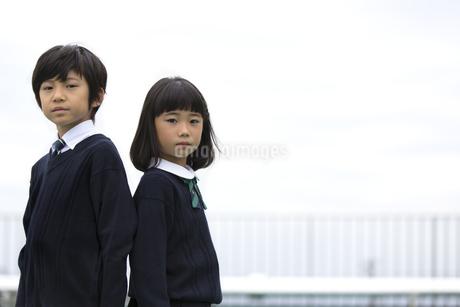 屋上に立つ小学生の男女のポートレートの写真素材 [FYI02968629]