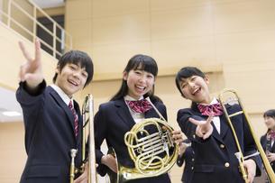 楽器を持ってポーズをとる男子学生と女子学生の写真素材 [FYI02968630]