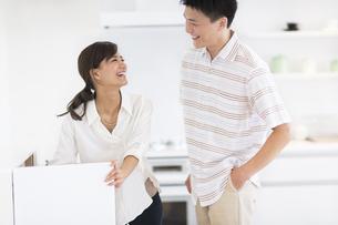 キッチンで笑い合う男性と女性の写真素材 [FYI02968631]