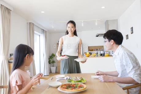 家族に食事を用意する母親の写真素材 [FYI02968638]
