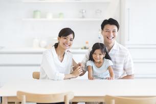 ダイニングテーブルで笑い合う家族の写真素材 [FYI02968639]