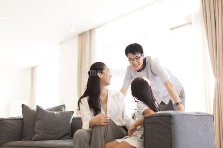 ソファーに座って笑い合う家族の写真素材 [FYI02968640]