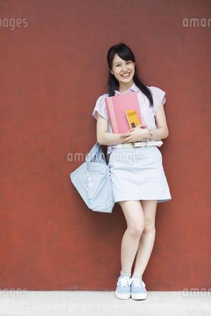 赤い壁の前で微笑む女子学生のポートレートの写真素材 [FYI02968641]