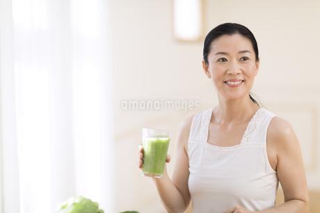 スムージーを手に微笑む女性の写真素材 [FYI02968643]
