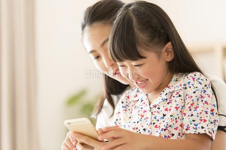 スマートフォンを見て楽しむ親子の写真素材 [FYI02968646]