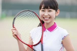テニスラケットを持って笑う女子学生の写真素材 [FYI02968649]