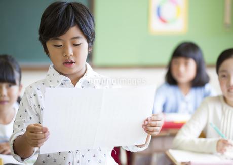授業中に作文を読む小学生の男の子の写真素材 [FYI02968651]