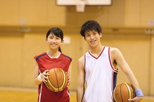 バスケットボールを持って微笑む男子学生と女子学生の写真素材 [FYI02968654]