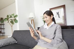 ソファーでスマートデバイスを見て微笑む女性の写真素材 [FYI02968655]
