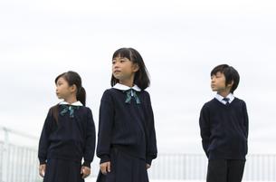 屋上に立って遠くを眺める小学生たちの写真素材 [FYI02968668]