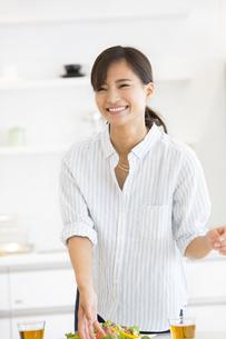 ダイニングテーブルで料理の準備をする女性の写真素材 [FYI02968675]