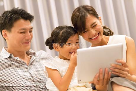 ソファーでタブレットPCを見る家族の写真素材 [FYI02968678]
